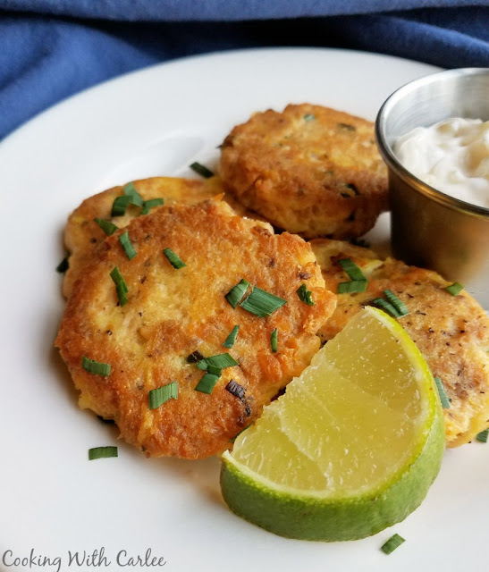 golden salmon patties with chives, a lemon slice and tartar sauce
