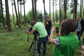 Naturführerin Edda fotografiert Robert, wie er das Fernglas vor die Kamera hält. Im Hintergrund zwei weitere Mitglieder des Fernsehteams.