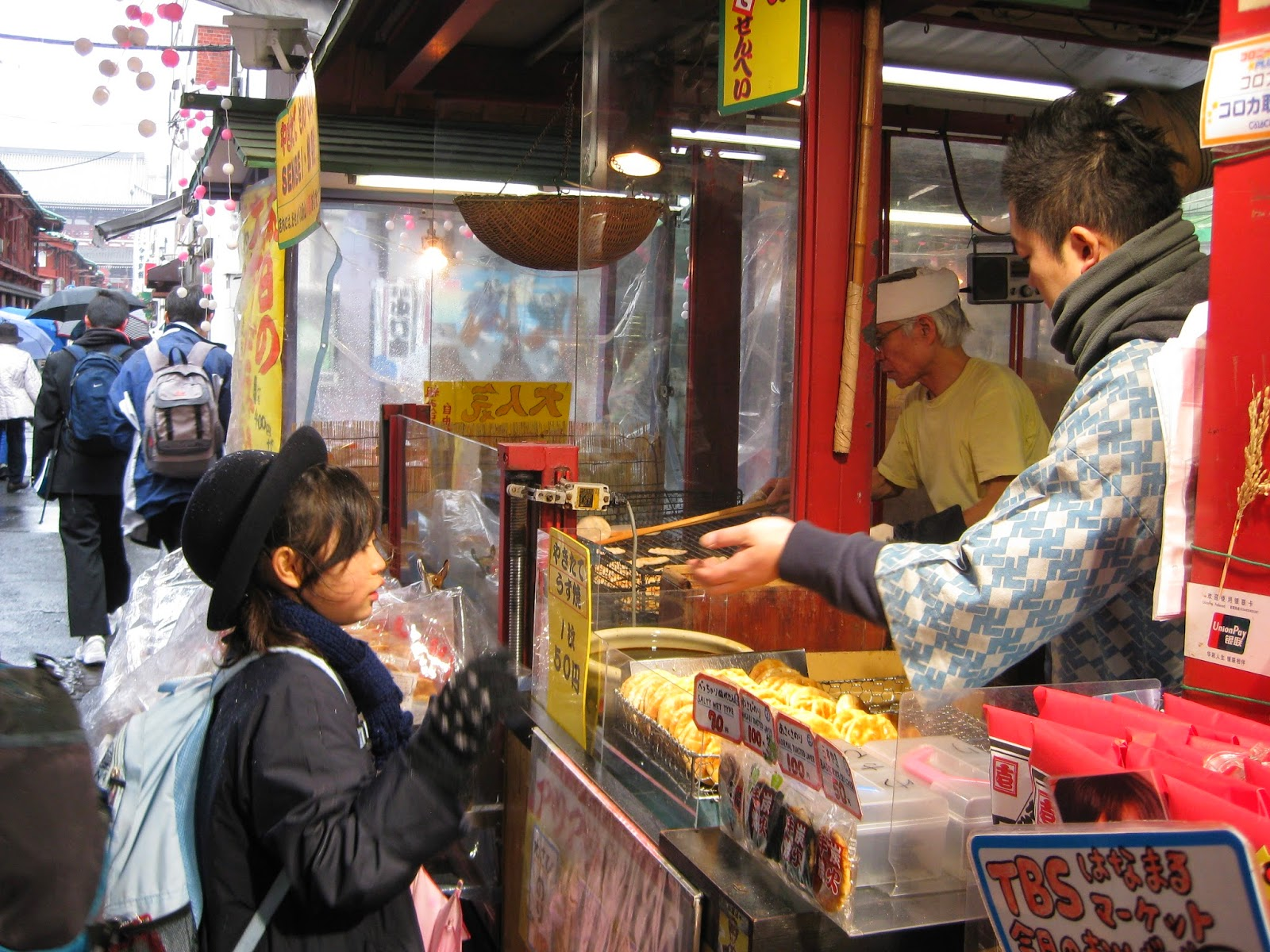 Tokyo - A schoolgirl (love her hat!) buys a rice cracker from a street vendor