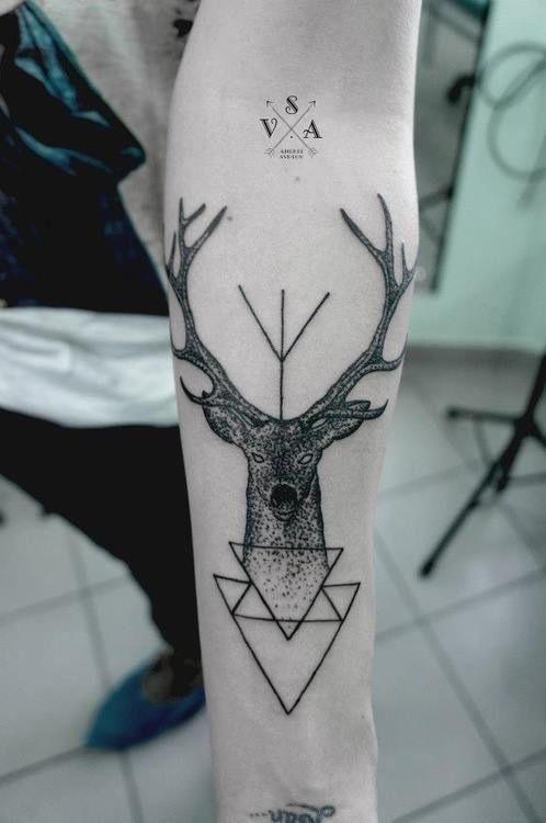 Vemos un antebrazo, con tatuaje de ciervo y de triángulos