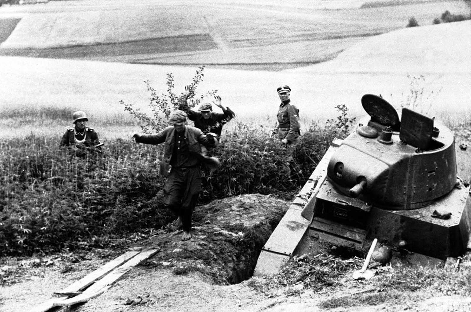 Russian snipers leave their hide-out in a wheat field, somewhere in Russia, on August 27, 1941, watched by German soldiers. In foreground is a disabled soviet tank.