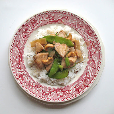 An overhead photo of cashew chicken on a red and white plate.