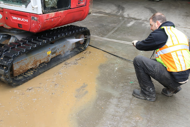 Man cleans mud out off Takeuchi excavator track