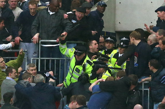 Police officers wield batons as they attempt to stop Millwall fans fighting amongst themselves