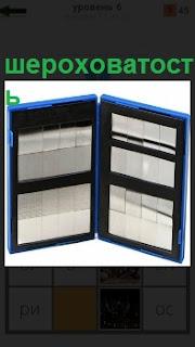Раскрытая коробка с шероховатостью внутри белого цвета стенки и кармашки, разделены полосками
