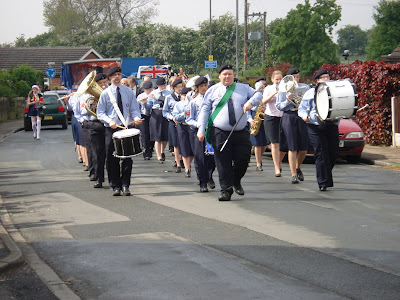 Brass band walking along the street in Gawthorpe Maypole procession