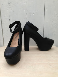 a pair of very high black platform heels