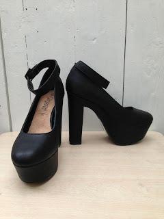 a pair of very high black platform heels