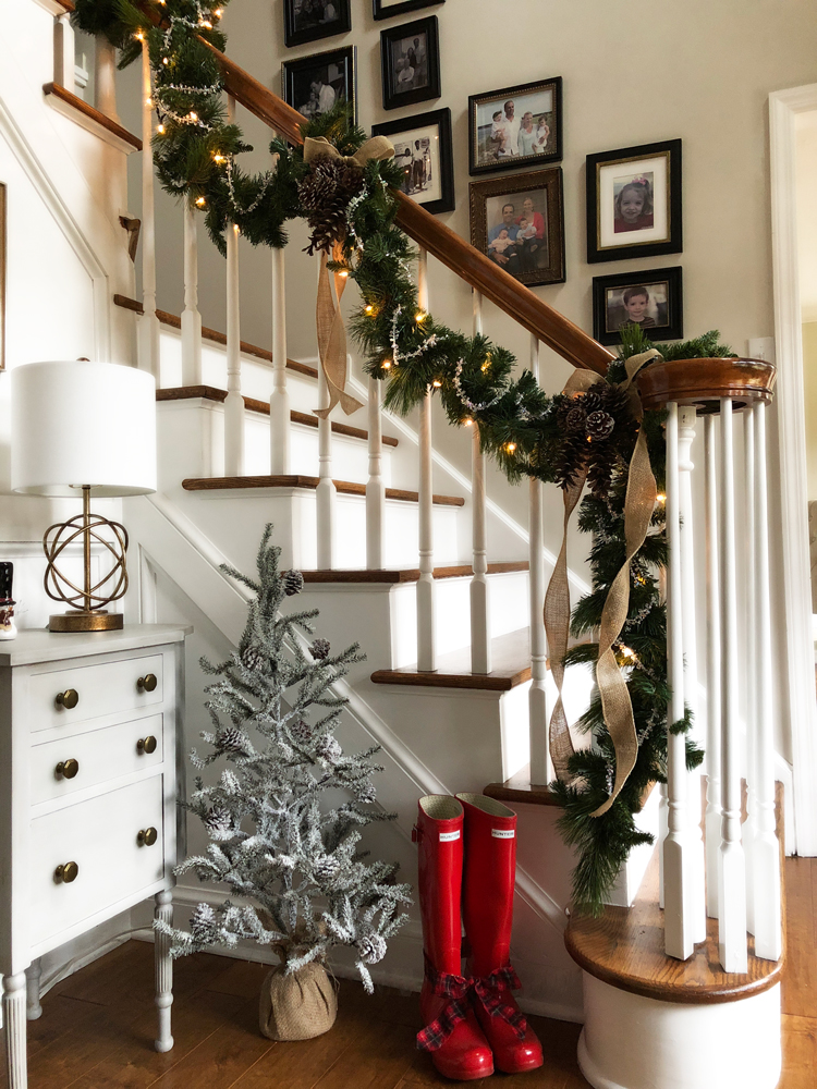 staircase with christmas garland pine cones and lights