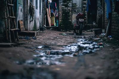 Calle de un suburbio llena de suciedad y objetos abandonados.