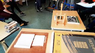 nas mesas encontram-se várias ferramentas: vários tipos de pepel, livros, cavalete pequeno, máquina de fazer massa