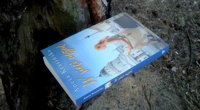To moje kolejne spotkanie z książkami Anety Krasińskiej poprzedni razy był udany, dlatego teraz podeszłam do książki z wielkim luzem i z pewnością, że nie powinnam się zawieść. Jednak prawda jest taka, że nigdy nie można mieć pewności, bo nawet ulubieni autorzy zawodzą...  W sieci uczuć ta opowieść o dziewczynie u progu dorosłości. Historia Justyny to przygody pisane przez życie. Dziewczyna mierzy się najpierw ze studiami, później z pracą, która niekoniecznie jest szczytem jej marzeń i z miłością, która nie zawsze idzie w parze ze zdrowym rozsądkiem. Przyjaźnie, miłostki, rodzinne rozterki to coś, czego nie zabraknie W sieci uczuć.  Książka ta jest typowym obyczajem, dlatego też pewnie nikogo nie zdziwi fakt, że autorka zastosowała narrację trzecioosobową. Nie przepadam za tym sposobem prowadzenia narracji, ponieważ najczęściej książki posiadające narratora wszechwiedzącego nie pozwalają mi wczuć się w postacie i zrozumieć ich emocje. Tym razem było podobnie. Mam jednak wrażenie, że problem tej książki nie leży tylko po stronie narracji. Myślę, że cała historia jest czymś, co zupełnie nie trafiło w mój gust.  W książce mamy Justynę, główną bohaterkę, osobę wokół, której całość fabuły się kręci i kobietę, która momentami potrafi postawić na swoim. Nie jest postacią przerysowane, sztuczną. Kobieta taka jak my wszystkie. W dorosłym życiu przyszło jej się mierzyć z problemami, które stają na drodze większości z nas, brak pracy, brak perspektyw, źle ulokowane uczucia. Książkę czyta się lekko, rozumiem, co chciała przekazać autorka. Agata Krasińska udowodniła, że życie to nie tylko szczęście, ale również gorycz porażki, trudne decyzje, niespełnione ambicje i pragnienia. Jednak całe konstrukcja książki nie koniecznie do mnie przemawia. Autorka pokusiła się na opowieść w formie zbitek różnych wydarzeń, które teoretycznie łączą się w spójną całość, ale jednak ja, jako czytelnik, miałam wrażenie przeskoków między scenami, wydarzeniami, a nawet pomiędzy latami poszczególnych s