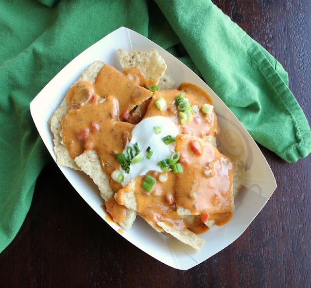 dish of nachos topped with tailgate queso, sour cream and green onions
