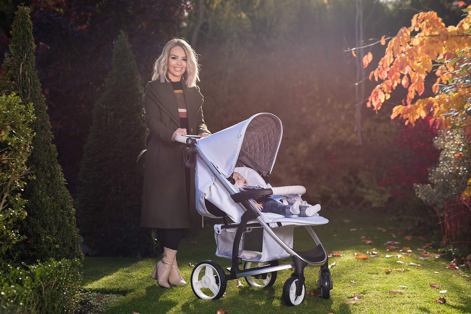 katie piper standing with a light blue buggy