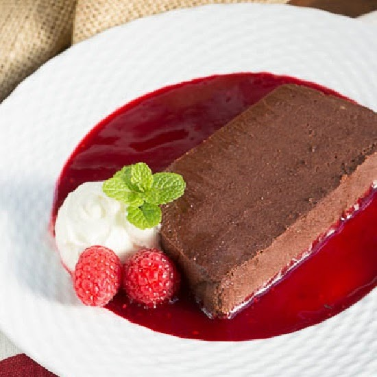 Side view of chocolate terrine with raspberry sauce on a white plate.