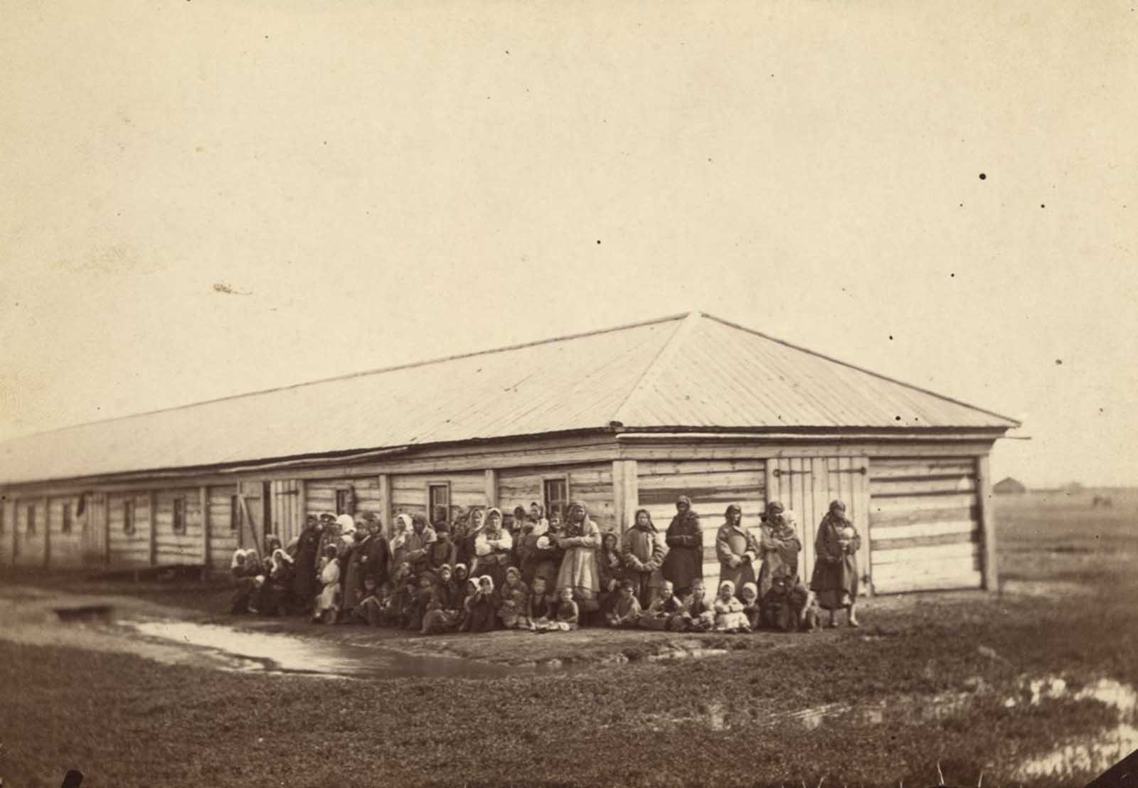 Women and children exiles stand in front of their barracks.