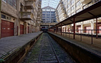 Perspective view down train tracks inside building