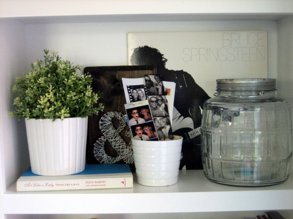 I love how these old photo booth photo strips lend a fun design element to this shelf.