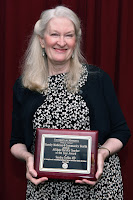 Dr. Coffin smiles and holds her award plaque