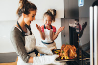 a woman pulling a turkey out of the oven with a big smile and young girl in background jumping for joy
