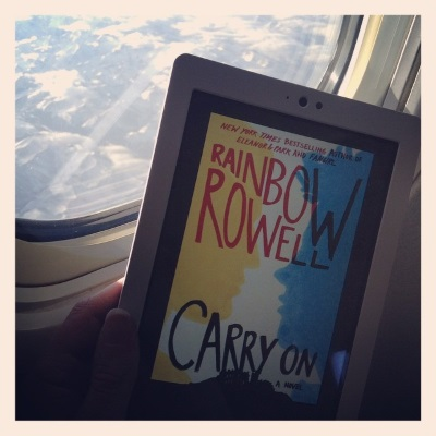 The cover of Carry On, featuring the yellow and blue silhouettes of two boys poised to kiss, appears on the screen of a white Kobo. Behind it, mountains are visible far below through an airplane window.