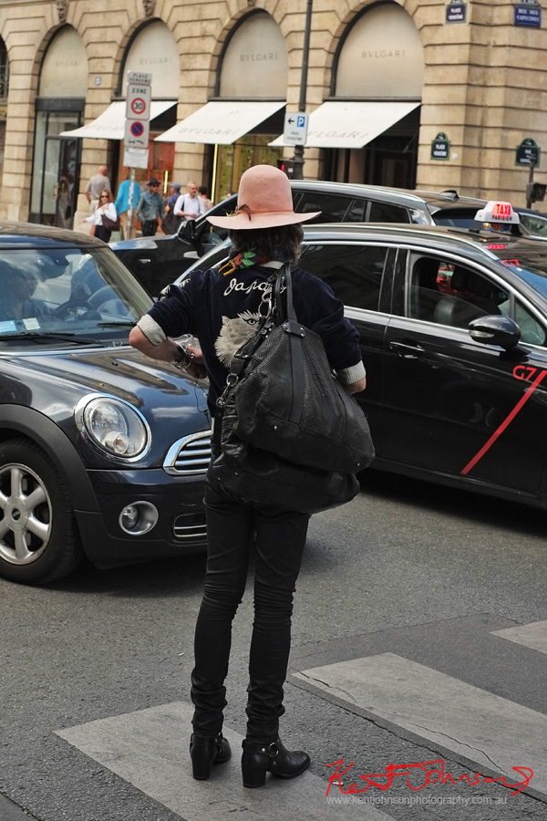Back view - Men's style on the streets of Paris - Rock and Roll look - Boots jeans, leather bags, Asian motif blouson, beads, earing, felt hat. Photographed at Paris-Vendôme by Kent Johnson for Street Fashion Sydney.