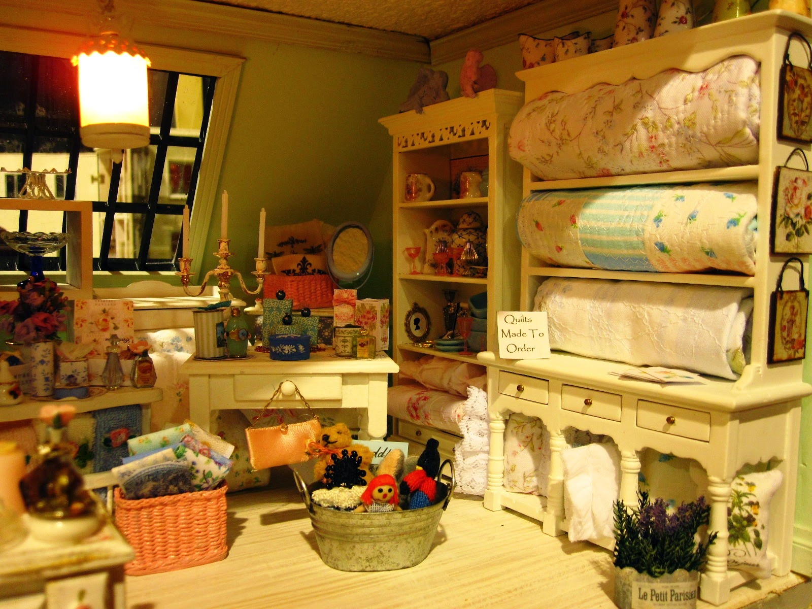 Modern miniature shabby chic shop display of linens and quilts on cream shelves.