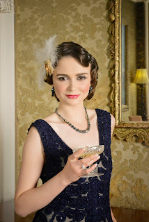 Girl styled as a 1920's style flapper with finger waved hair, vintage makeup, with a feather hair accessory