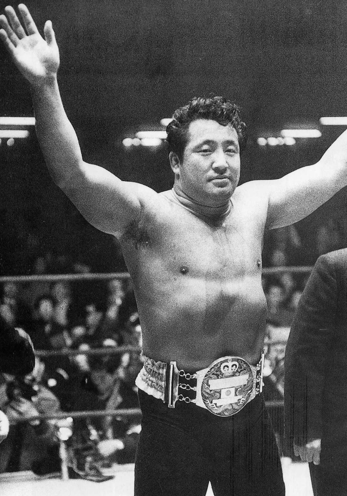 プロレスのリングでチャンピオンベルトを着けて両手を上げる力道山