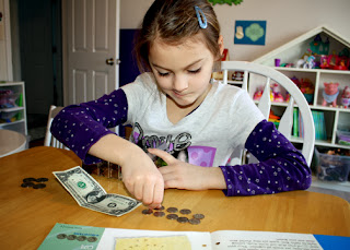 Tessa identified various paper bills and their worth. She also counted out the proper number of coins to equal a dollar.