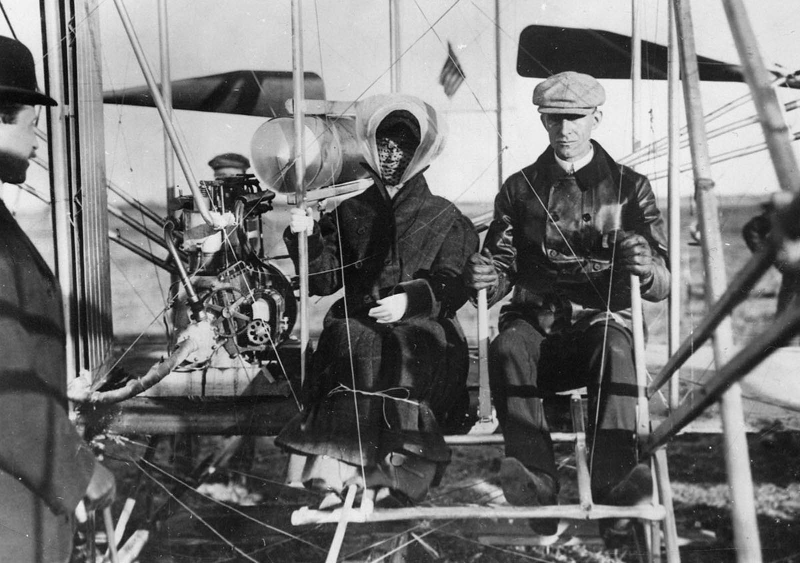 Siblings Orville Wright, Katharine Wright, and Wilbur Wright at Pau, France. Miss Wright about to be taken for her first ride in an airplane. February 15, 1909.