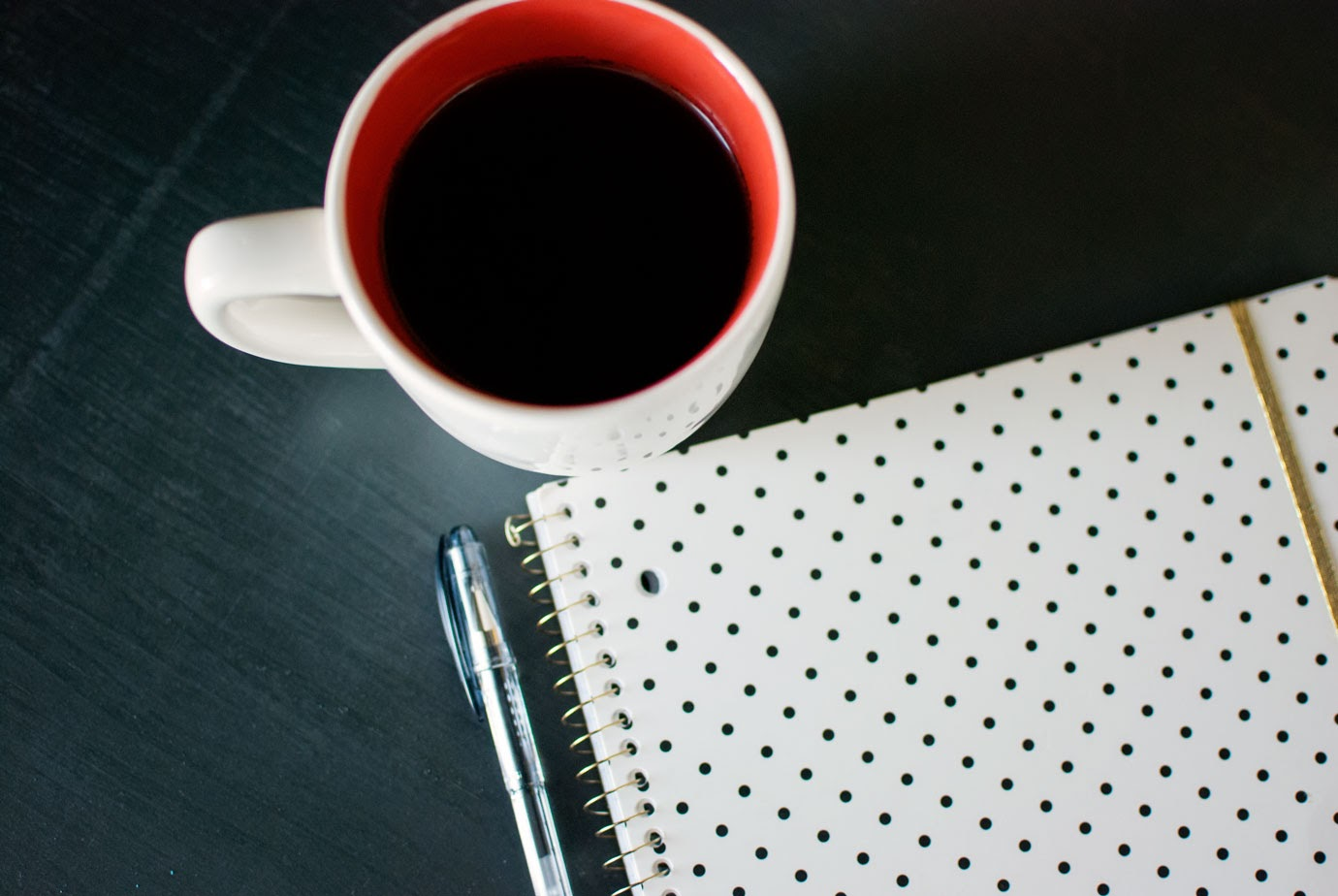 Coffee in a mug next to a black and white polka dot notebook and pen