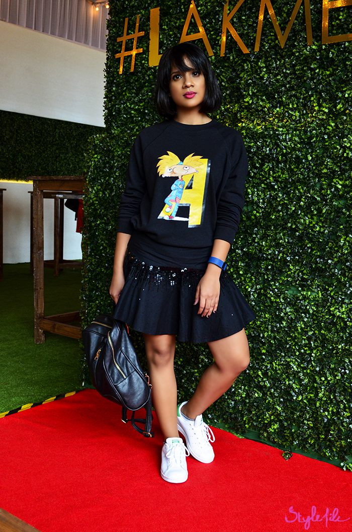 A girl shows off her street style at Lakme Fashion Week in a sweatshirt, mini skirt, adidas originals stan smith sneakers and backpack