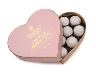 Several bright pastel pink spherical chocolate truffles in a light pink heart shaped box next to a bright pink heart shaped lid on a white background.