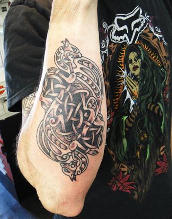 chico con tatuaje celta de perros en el antebrazo