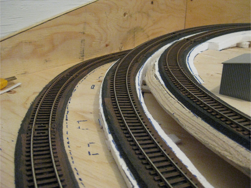 Three curved tracks with their ties painted with brown acrylic paint