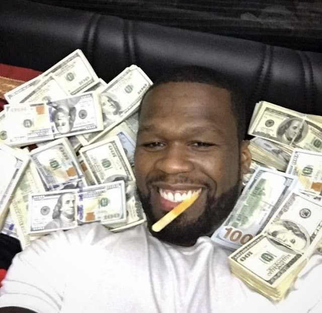 50 Cent poses with stacks of money