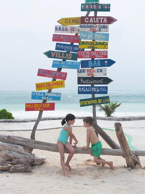 Dos niños en la playa frente a unos carteles de colores con distancias a ciudades del mundo
