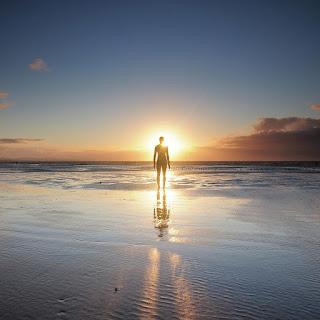 Μοναχικός άντρας στην παραλία που κοιτάζει τον ήλιο.