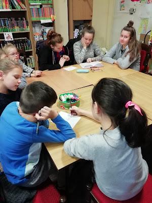 Uczestnicy zajęć feryjnych siedzą wokół stołu, sluchają fragmentu opowiadania i rozwiązują krzyżówkę.