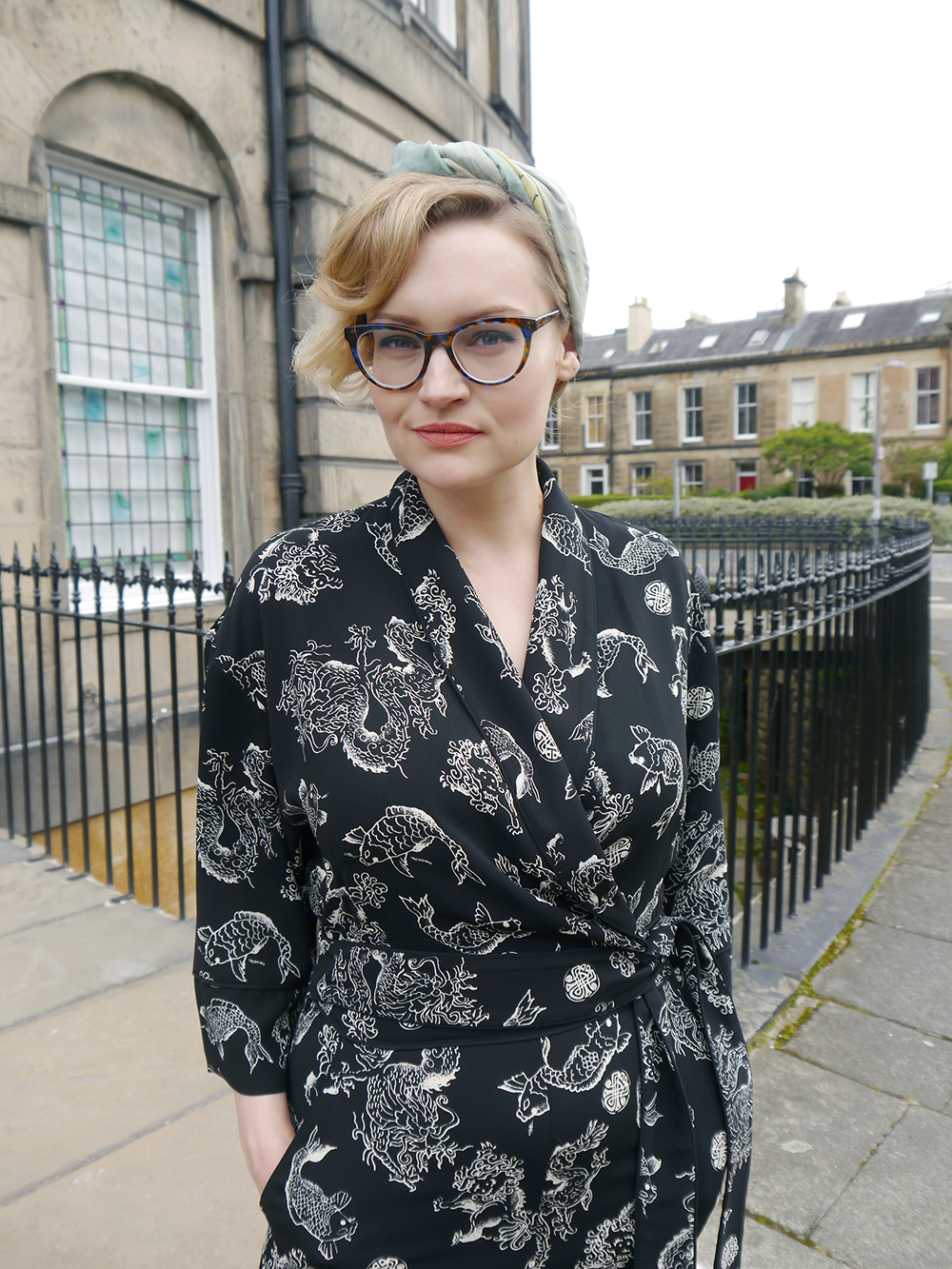 British fashion blogger Kimberley from Wardrobe Conversations wears a black print Biba jumpsuit, headscarf and CrossEyes glasses for an easy Sunday cocktail look