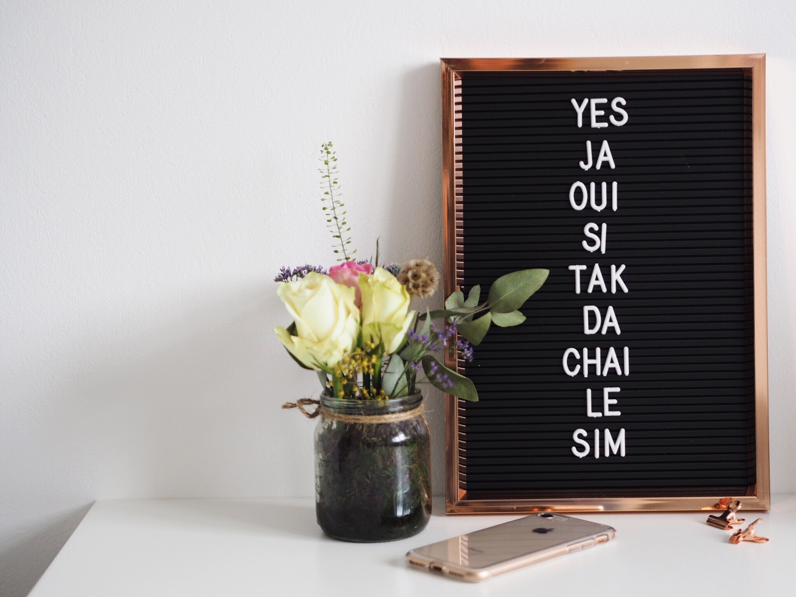 Copper & Black Letter Board with Yes in Multiple Languages with iphone 8, rose flower posy on a white desk