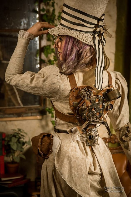 Steampunk woman in mad hatter top hat, steampunk backpack, jacket, skirt, corset. Women's steampunk costumes and fashion