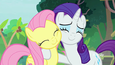 Fluttershy and Rarity hugging, both smiling with closed eyes, in front of greenery