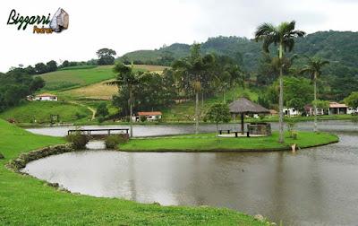 Construção de lago é com pedra moledo com a ilha e o quiosque de piaçava, churrasqueira de pedra e a ponte de pedra em sítio em Nazaré Paulista-SP.