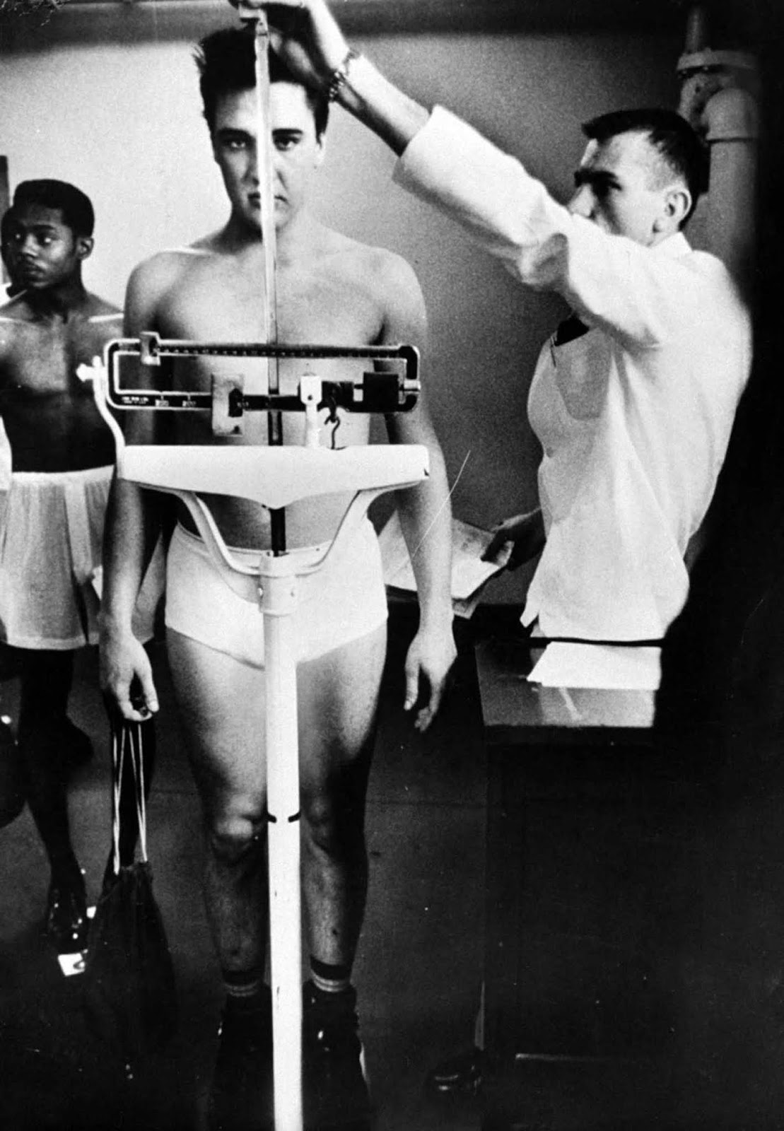Presley clad only in his skivvies as he stands on a scale while an Army doctor measures his height at a pre-induction physical examination at Kennedy Veterans Hospital.