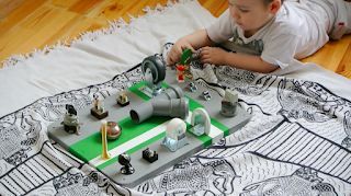 little boy on the floor playing with activity board