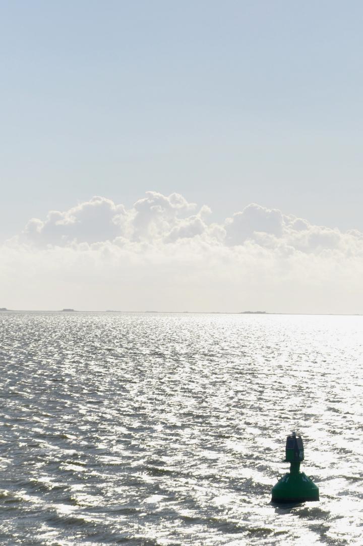 Gegenlichtaufnahme von der Nordsee mit Boje
