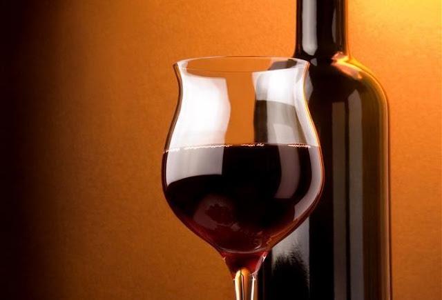 グラスに注がれた赤ワインとボトル