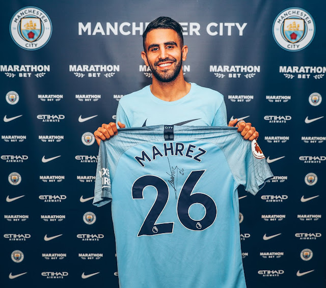Riyad Mahrez holds up a Man City Jersey as he completes his move to Etihad from Leicester city